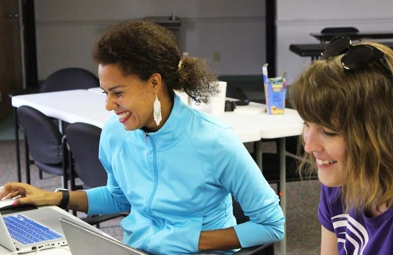 Two volunteers sitting next to each other and smiling while working on computers.