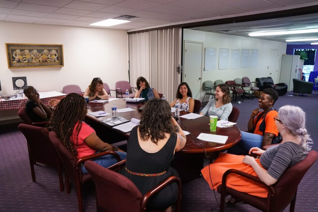 Clinic staff members and volunteers have a discussion at a conference table in the clinic.