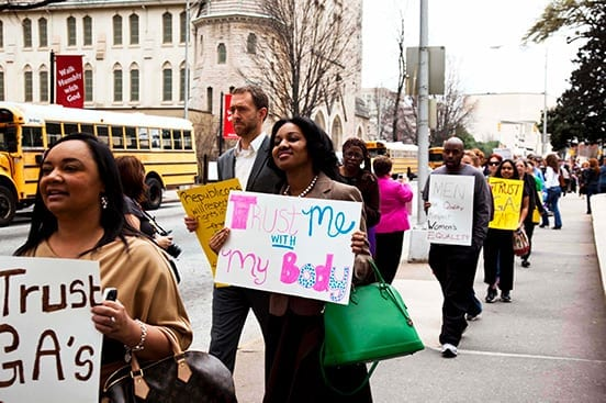 """Demonstrators march with signs at a rally, including one reading """"Trust me with my body."""""""