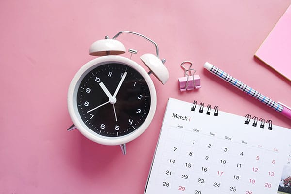 A close-up image of a clock and calendar