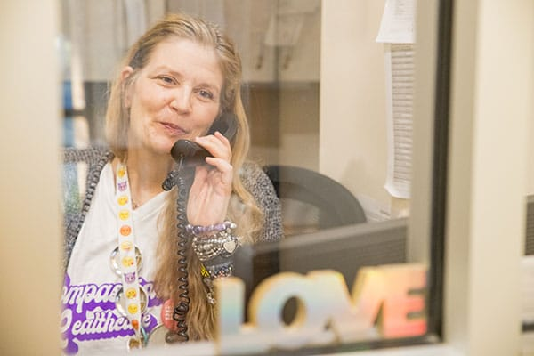 """A staff member wearing a """"Compassionate Healthcare since 1976"""" t-shirt smiles while holding a phone to their ear at the front desk of the clinic."""
