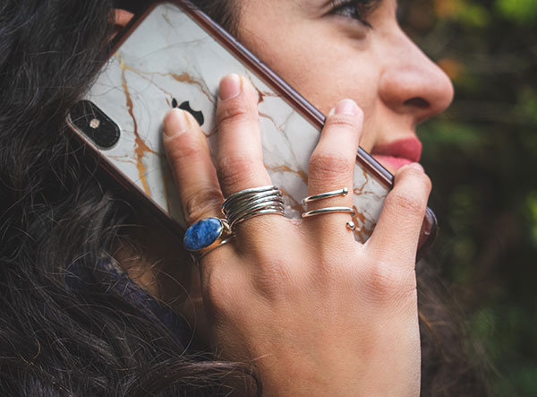 Close-up of model holding cell phone up to her ear.