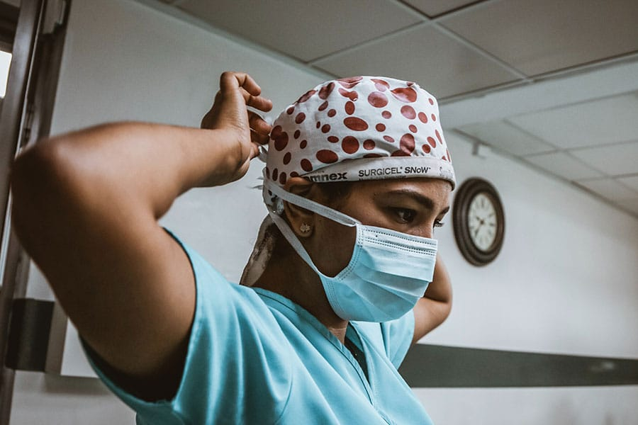 Model posing as staff member wearing scrubs, mask, and cap.