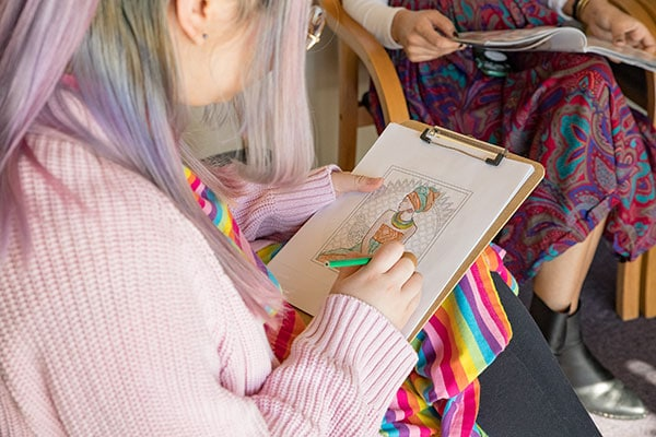 A model posing as a patient colors a picture while sitting in the clinic waiting area.