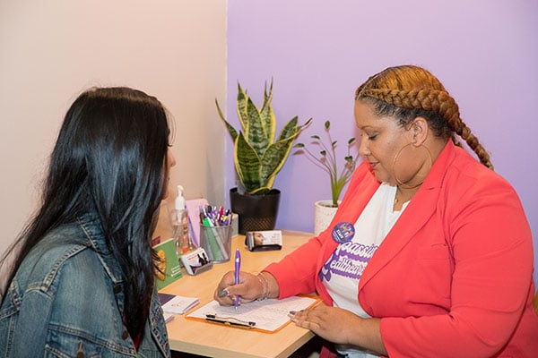 A clinic staffer sits at a desk filling out forms for a model posing as a patient.