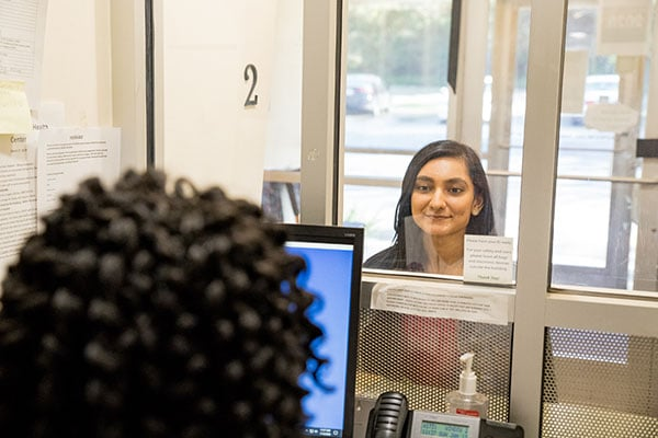 A model poses as a patient speaking with a staff member at the front desk.