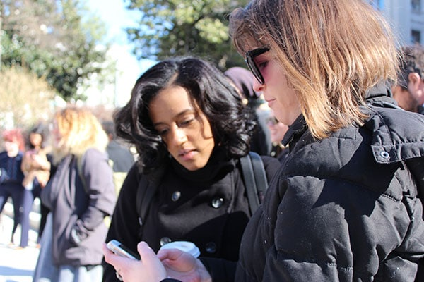 A staff member shows an intern something on their phone at an outdoor rally.