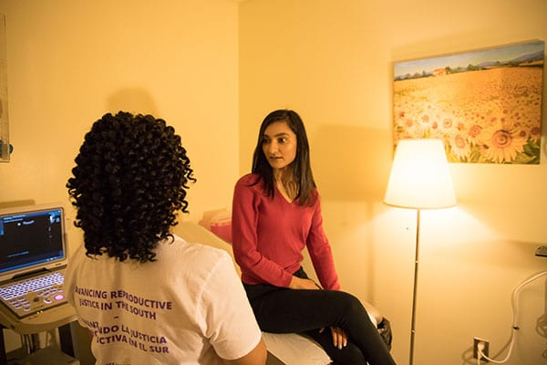 A clinic staffer speaks with a model posing as a patient.