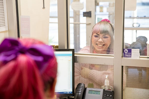 A model posing as a patient smiles at a staff member from behind the glass at the clinic's front desk.