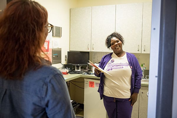 A clinic staffer smiles at a model posing at a patient with their back to the camera.