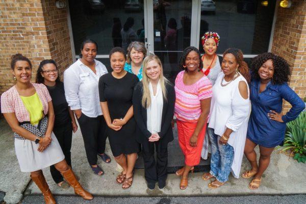 Feminist Women's Health Center team poses for a photo outside clinic doors.