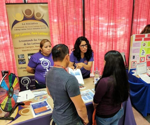 Two Lifting Latinx Voices Initiative members share information with event attendees at their table.
