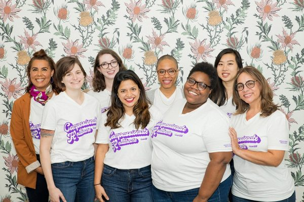 """Staff members pose wearing Feminist Women's Health Center t-shirts that read, """"Compassionate Healthcare since 1976"""""""