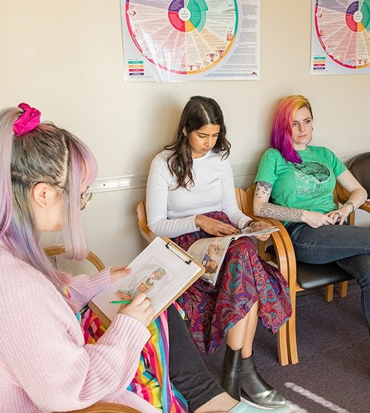Three models pose as patients in the waiting room
