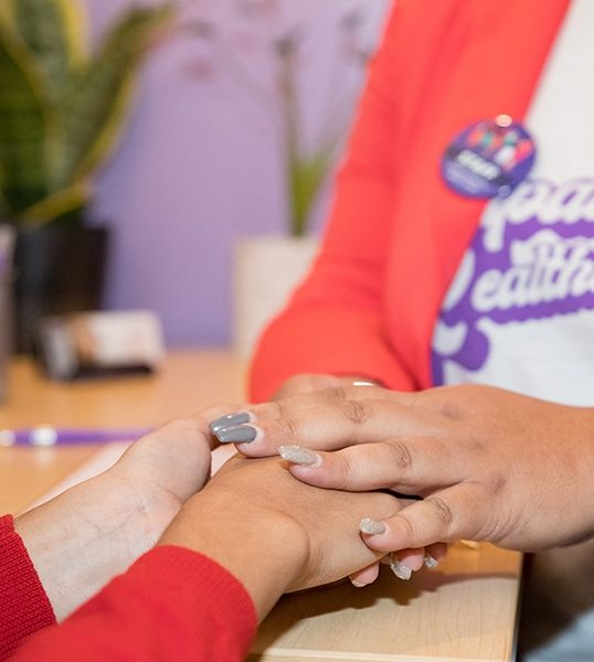 Close-up of a clinic staff member in a Feminist Women's Health Center t-shirt holding a patient's hand.