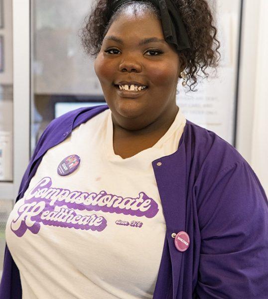 Clinic staff member smiles in a Feminist Women's Health Center t-shirt.