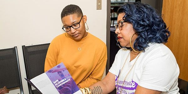 A clinic staffer presents a pamphlet to a model posing as a patient.