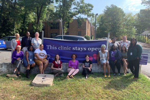 """Staff members and volunteers pose in front of the Feminist Women's Health Center with a banner that reads """"This clinic stays open."""""""