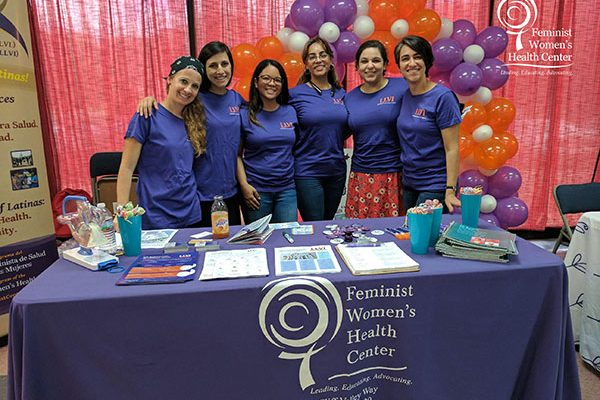 Members of the Lifting Latinx Voices Initiative team pose behind a Feminist Women's Health Center table at an event.