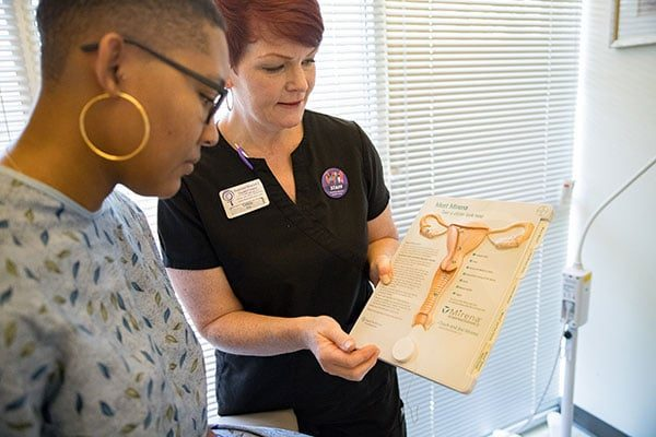 A clinic staffer shows a model posing as a patient an image of the female reproductive system.