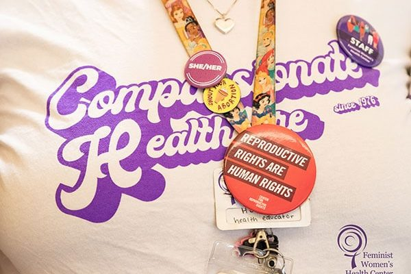 """A close-up image of a staff member wearing a """"Compassionate Healthcare since 1976"""" t-shirt."""