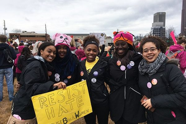 """Four smiling demonstrators holding a sign that reads """"Resist Hate. Trust Black Women."""""""