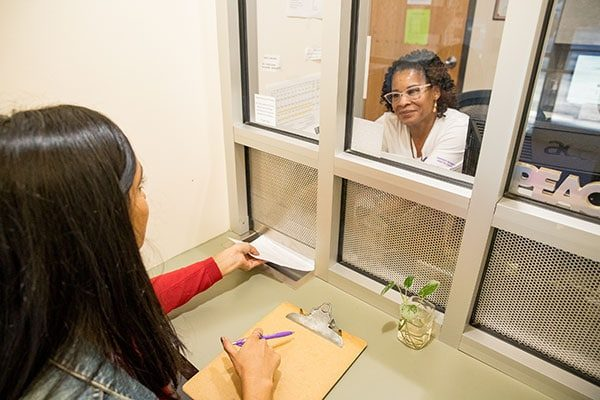 A staff member hands a model posing as a patient a form from behind the glass at the clinic's front desk.