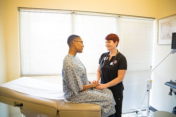 A clinic staffer speaks with a model posing as a patient in a procedure room.
